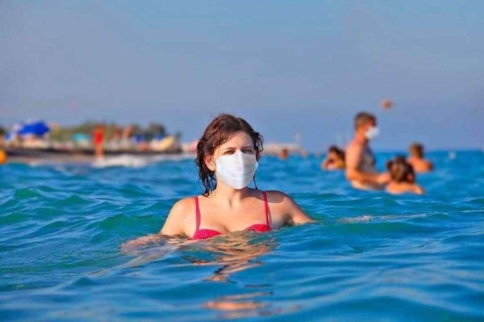 Foto di persone al mare mentre fanno il bagno con la mascherina